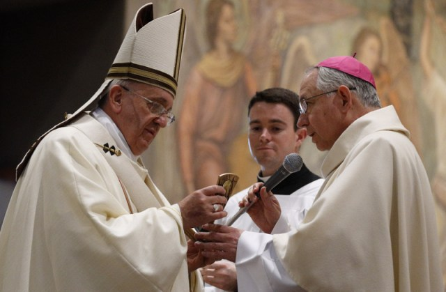 Pope Francis accepts a relic of Blessed Junipero Serra from Archbishop Jose H. Gomez of Los Angeles at the conclusion of Mass celebrated at the Pontifical North American College in Rome May 2. It was the first papal visit to the U.S. seminary since 1980. The pope said that while some people seem to relish the idea of listing Blessed Serra's defects, he wondered how many would have the courage he had to leave everything and preach the Gospel. (CNS photo/Paul Haring)