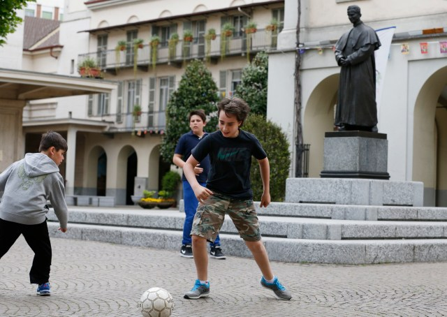 Children play soccer near a statue of St. John Bosco in a courtyard of the Sanctuary of Our Lady of Help of Christians in Turin, Italy. The sanctuary was the site of St. Bosco's home for poor and abandoned boys. Pope Francis will commemorate the 200th anniversary of the birth of St. Bosco during his June 21-22 visit to Turin. (CNS/Paul Haring)