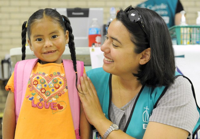 Sister Leticia Benavides of the Missionaries of Jesus, a counselor at Catholic Charities of the Rio Grande Valley, greets a happy immigrant girl at a respite center at Sacred Heart Church in McAllen, Texas. The girl had just taken a shower and put on clean clothes after a weeks-long journey from Central America to the center for immigrants. (CNS/Cesar Riojas, The Valley Catholic)