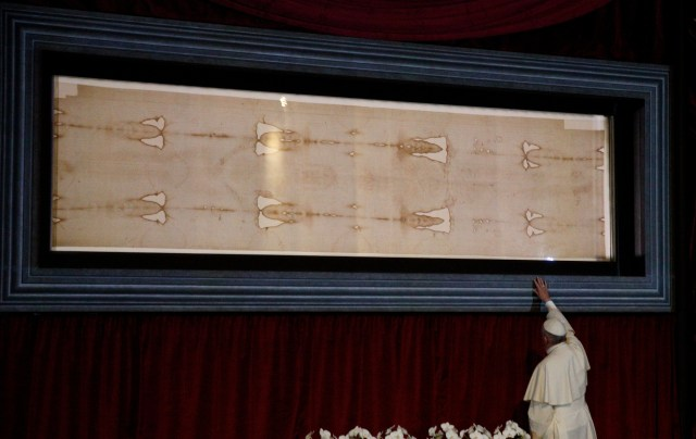 Pope Francis touches the case holding the Shroud of Turin after praying before the cloth in the Cathedral of St. John the Baptist in Turin, Italy, June 21. (CNS photo/Paul Haring)