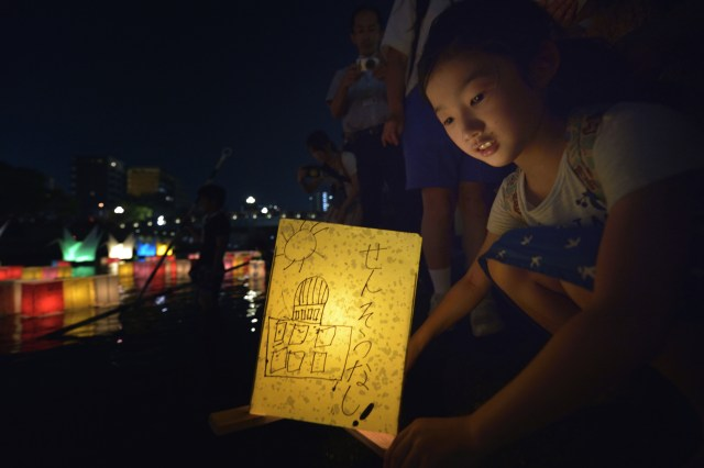 A girl sets a floating candle lantern on the river Aug. 6 in Hiroshima, Japan. The lanterns, thousands of which were launched on the 70th anniversary of the atomic bombing of the city, bear handmade messages and drawings, conveying each person's prayers for peace and comfort for the victims of the violence. (CNS/Paul Jeffrey)