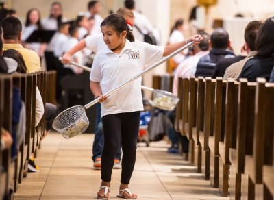 Hispanic Youth Group member Yelixa Hernandez helps collect donations during Mass at St. Willebrord Church in Green Bay, Wis. Hispanics are