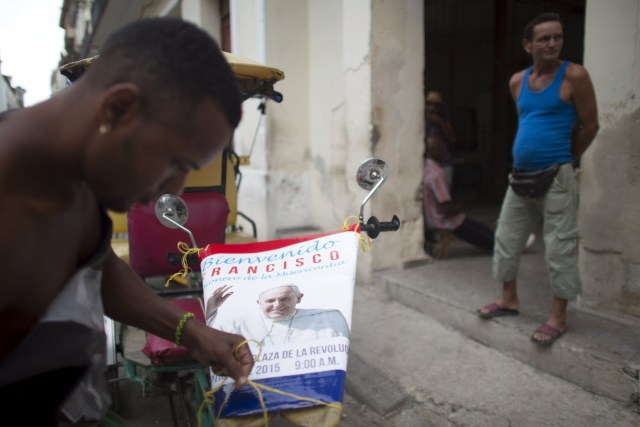 A pedicab driver in Havana Aug. 21 attaches a poster advertising the visit of Pope Francis to Cuba. The pope is scheduled to visit Cuba Sept.19-22. (CNS photo/Alexandre Meneghini, Reuters)