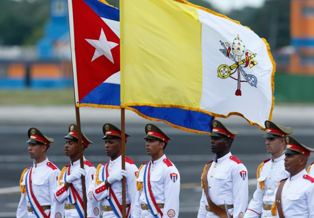 An honor guard carries the Cuban and Vatican flags during the arrival ceremony for Pope Francis at Jose Marti International Airport in Havana Sept. 19. (CNS/Paul Haring)