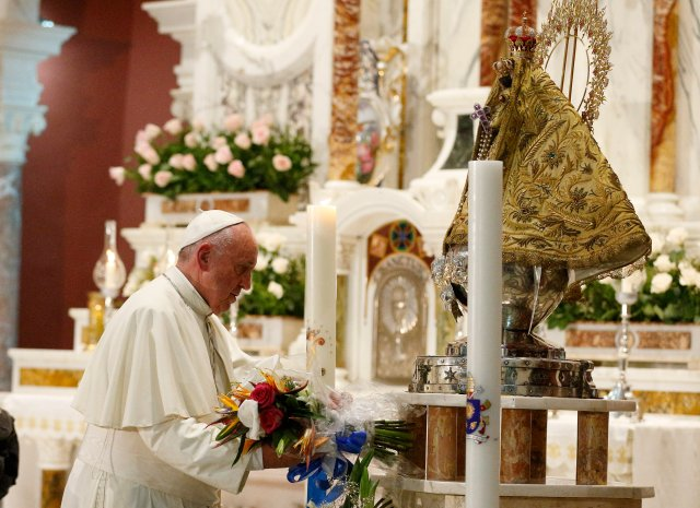 Pope Francis places flowers at the statue of Our Lady of Charity, patroness of Cuba, in the Minor Basilica of the Shrine of Our Lady of Charity in El Cobre, Cuba, Sept. 21. (CNS/Paul Haring)