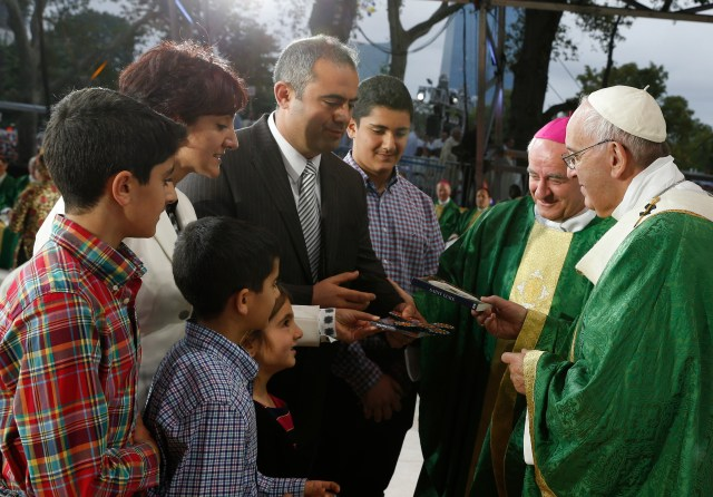 Pope Francis gives a copy of the Gospel of Luke to a family during the closing Mass of the World Meeting of Families on Benjamin Franklin Parkway in Philadelphia Sept. 27. (CNS photo/Paul Haring)