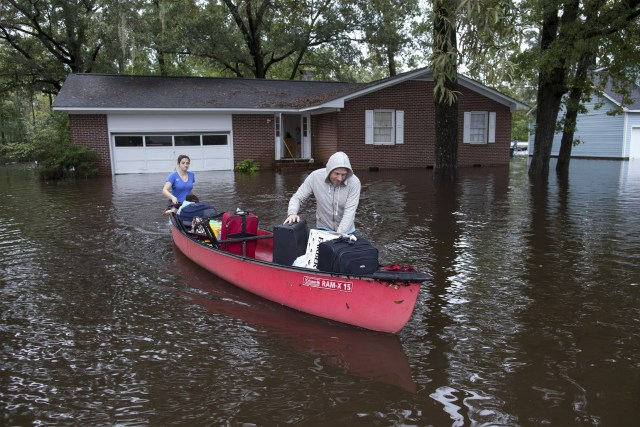 Residents use a canoe to evacuate a home surrounded by floodwaters in Conway, S.C., Oct. 5. (CNS/Reuters)