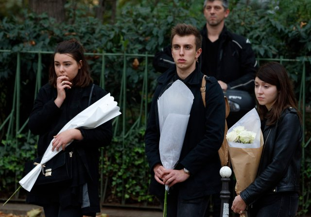 Young people hold flowers as they look at the Bataclan music hall in Paris Nov. 16. (CNS/Paul Haring)