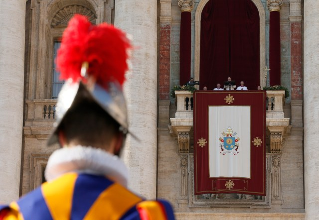 "A Swiss Guard is seen as Pope Francis deliver his Christmas blessing ""urbi et orbi"" (to the city and the world) from the central balcony of St. Peter's Basilica at the Vatican Dec. 25. (CNS/Paul Haring)"