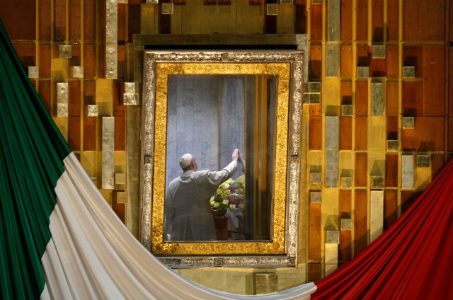 """Pope Francis touches the original image of Our Lady of Guadalupe after celebrating Mass in the Basilica of Our Lady of Guadalupe in Mexico City Feb. 13. The Marian image was rotated for the pope to pray in the """"camarin"""" (""""little room"""") behind the main altar. (CNS/Paul Haring)"""
