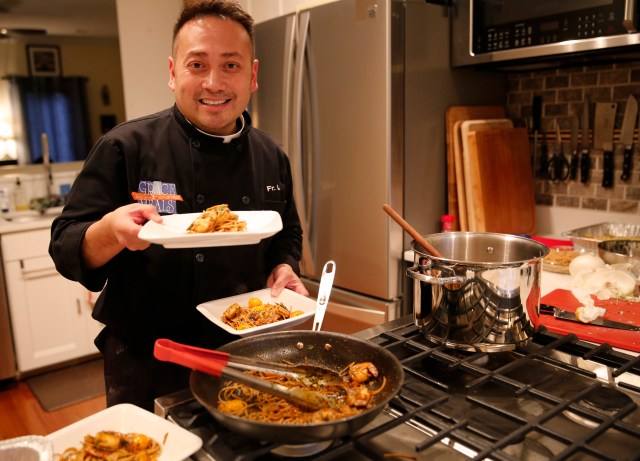 Celebrity chef Father Leo Patalinghug displays a Lenten seafood pasta meal he prepared in his Baltimore kitchen. (CNS/Chaz Muth)