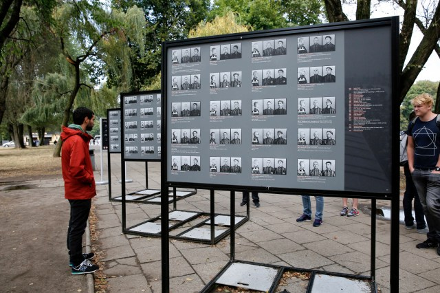 Visitors look over displays of photographs of concentration camp prisoners outside the Auschwitz-Birkenau Memorial and State Museum in Oswiecim, Poland. (CNS/Nancy Wiechec)