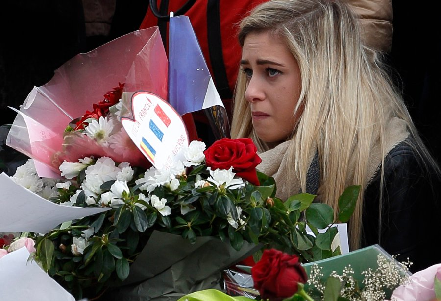 A woman observes a moment of silence in Republique square in Paris Nov. 16 after last fall's terror attacks in France. (CNS/Paul Haring)