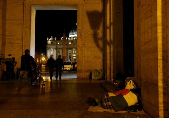 A homeless person sleeps outside the Vatican press office near St. Peter's Square in 2014. (CNS/Paul Haring)