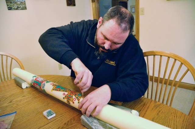 Father Aaron Jenkins, pastor of St. Michael Parish in Greenfield, Ind., puts the final touches on an Easter candle that he decorated. (CNS/Sean Gallagher, The Criterion)