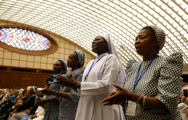 Nuns sing as they wait for Pope Francis' arrival at an audience with the heads of women's religious orders in Paul VI hall at the Vatican May 12. During a question-and-answer session with members of the International Union of Superiors General, the pope indicated his willingness to establish a commission to study whether women could serve as deacons. (CNS/Paul Haring)