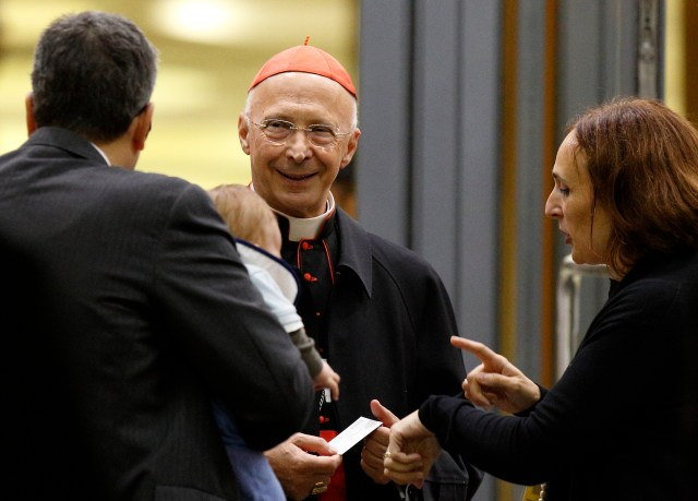 Cardinal Angelo Bagnasco, president of the Italian bishops' conference, talks with a married couple as they leave the opening session of the Synod of Bishops on the family at the Vatican last October. (CNS file/Paul Haring)