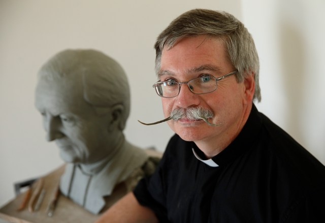 Edward Gibney, a Canadian seminarian and sculptor from Saskatchewan, poses near an almost completed statue of Msgr. Roderick Strange in his makeshift studio at the Pontifical Beda College in Rome June 15. Gibney is sculpting at the college while finishing studies for the priesthood. (CNS/Paul Haring)