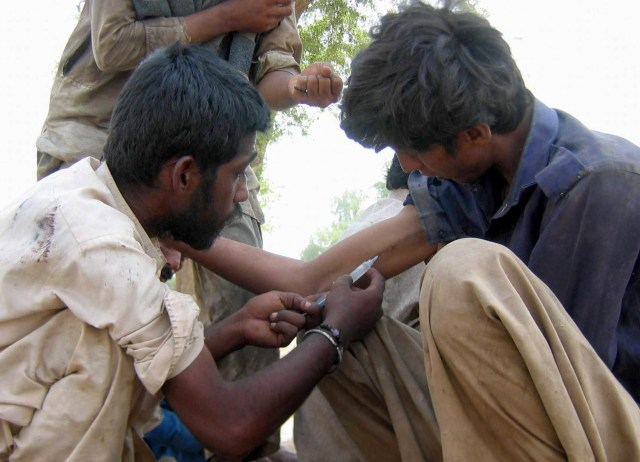 A Pakistani man injects a heroin-filled syringe into a man in 2011 on the streets in Multan. Pope Francis has requested a special study session at the Vatican to look at how to solve the growing problem of drug abuse, especially narcotics. (CNS photo/MK Chaudhary, EPA)