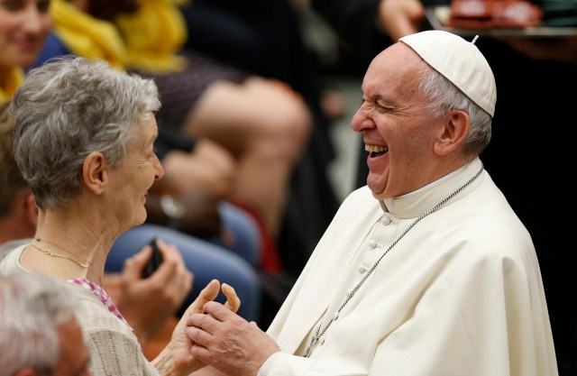 Pope Francis laughs as he greets a woman during an audience with 200 people living in difficult or precarious situations. (CNS/Paul Haring)