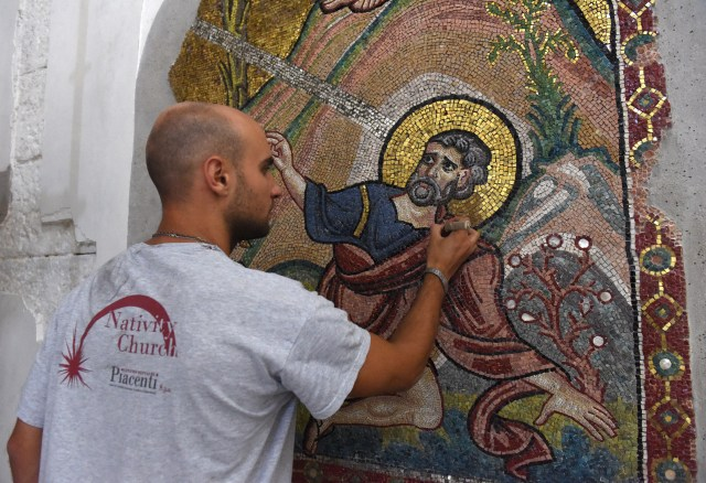 A worker from the Piacenti restoration center works on a mosaic in the Church of the Nativity July 5 in Bethlehem, West Bank. Restoration specialists from the center completed their work in June. (CNS/Debbie Hill)
