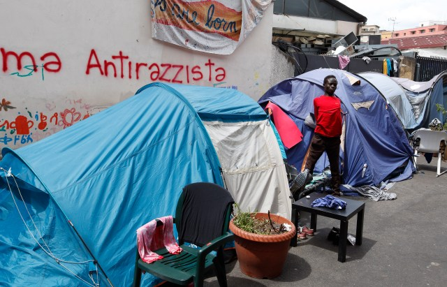 An African refugee stretches on a street in Rome July 14 outside tents where they dwell temporarily. (CNS photo/Paul Haring)