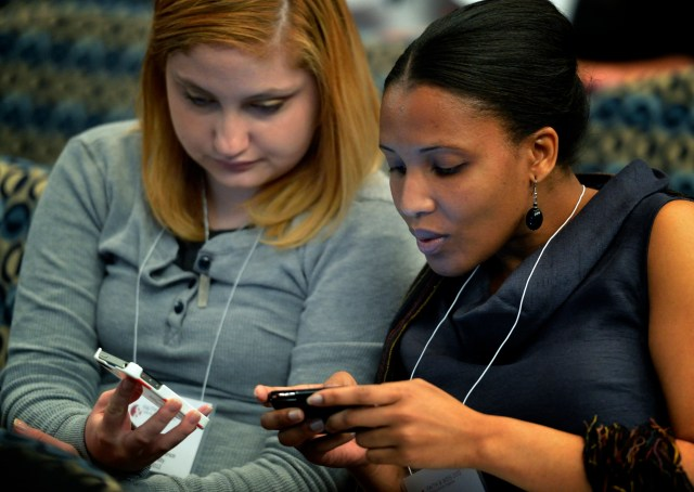 Women view their phones during a conference in Washington. (CNS/Paul Jeffrey)