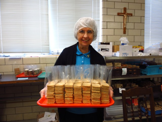 Benedictine Sister Romaine Kuntz carries a tray of finished Hildegard cookies Sept. 13 at a monastery run by the Sisters of St. Benedict in Ferdinand, Ind., in time for St. Hildegard's Sept. 17 feast day. (CNS/Katie Breidenbach)