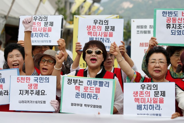 """South Korean activists shout slogans as they hold up banners reading, """"Government needs to prepare the Nuclear Road map for the nation,"""" during a Sept 12 protest in Seoul against North Korea's fifth nuclear test. (CNS photo/Jeon Heon-Kyun, EPA)"""