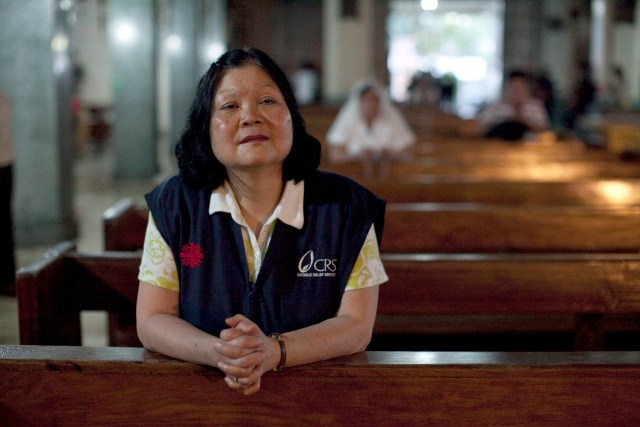 Carolyn Woo, outgoing CEO of Catholic Relief Services, reflects after a 2014 Mass at a church in Tacloban, Philippines. She was visiting CRS programs assisting people affected by Typhoon Haiyan, which hit the Philippines in November 2013. (CNS/courtesy Catholic Relief Services)