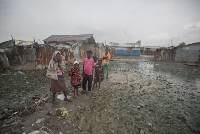 Hatian children stand in mud outside their homes Oct. 3 in Cite Soleil, a slum in Port-au-Prince, hours before Hurricane Matthew hit the island nation. (CNS photo/Bahare Khodabande, Reuters)