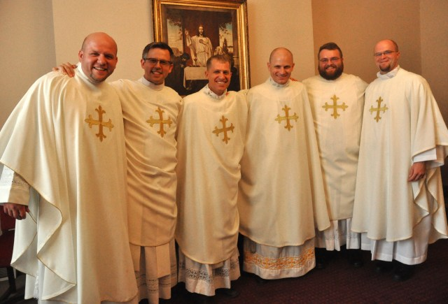 Fathers Andrew and Benjamin Syberg, Anthony and John Hollowell, and Doug and David Marcotte pose June 25 in the rectory of SS. Peter and Paul Cathedral in Indianapolis after Father Anthony was ordained a priest. That ordination rounded out three sets of brothers ordained for the Archdiocese of Indianapolis since 2009. (CNS/Sean Gallagher, Criterion)