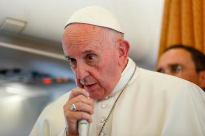 Pope Francis answers questions from journalists aboard a papal flight last year. (CNS/Paul Haring)