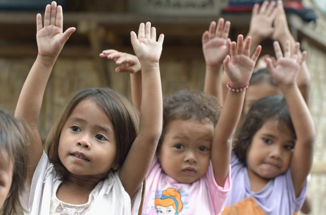 Indigenous children displaced by paramilitary violence exercise at the beginning of a school day on a church compound in Davao, on the southern Philippine island of Mindanao. Hundreds of indigenous are living in the church center, afraid to return home. (CNS/Paul Jeffrey)