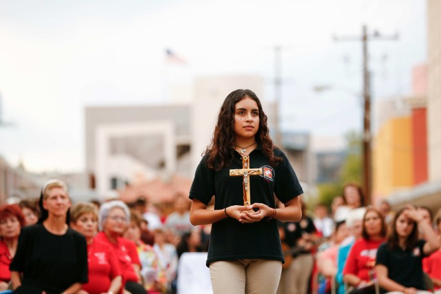 A young woman carries a crucifix in the offertory procession during Mass at the international border in Nogales, Ariz., Oct. 23. The cross was presented as an offertory gift to recall migrants who have died in the deserts of Arizona. (CNS/Nancy Wiechec)