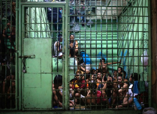 Alleged drug traffickers and users sit behind bars in Manila, Philippines. (CNS/EPA)