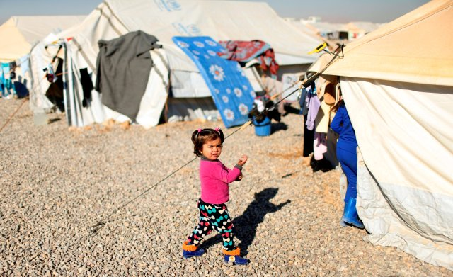 A displaced Iraqi child walks outside tents Dec. 9 at the Hassan Sham camp near Mosul. (CNS/Reuters)
