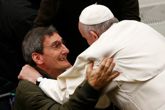 Pope Francis greets a man while meeting the disabled during his general audience in Paul VI hall at the Vatican Dec. 14. He also was honored with birthday cakes in anticipation of his 80th birthday Dec. 17. (CNS/Paul Haring)