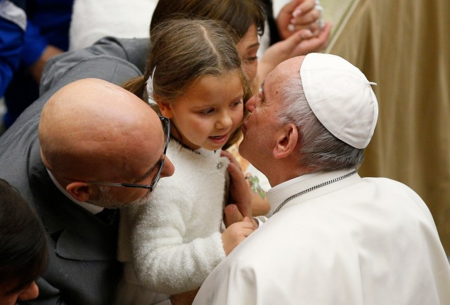 Pope Francis kisses a young girl during his general audience in Paul VI hall at the Vatican Dec. 14. (CNS/Paul Haring)