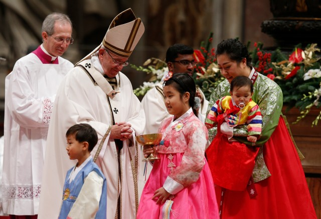 Members of the Lee family present offertory gifts to Pope Francis during Christmas Eve Mass in Peter's Basilica at the Vatican Dec. 24. (CNS/Paul Haring)