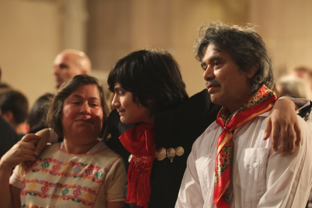 """Samuel Catalan, middle, holds on to his mother, Alejandra Catalan, and father, Francisco Catalan, at a Dec. 10 Mass for the feast of Our Lady of Guadalupe at the Basilica of the National Shrine of the Immaculate Conception in Washington. Washington Auxiliary Bishop Mario E. Dorsonville told the largely immigrant crowd that the Catholic Church stands with them in """"these difficult moments"""" of uncertainty about immigration matters in the country. (CNS photo/Rhina Guidos)"""
