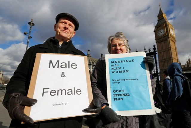 Christian activists Jonathan Longstaff and Jenny Rose, both from London, protest outside Parliament before a vote on same-sex marriage in London in 2013. (CNS/Reuters)