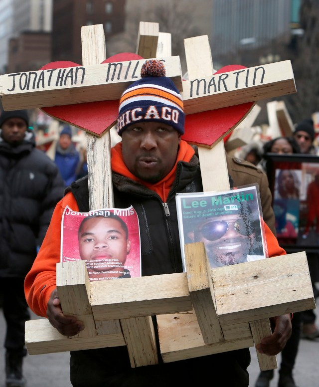 A man carries crosses with names of victims of gun violence during a Dec. 31 march in downtown Chicago. (CNS/Karen Callaway, Catholic New World)