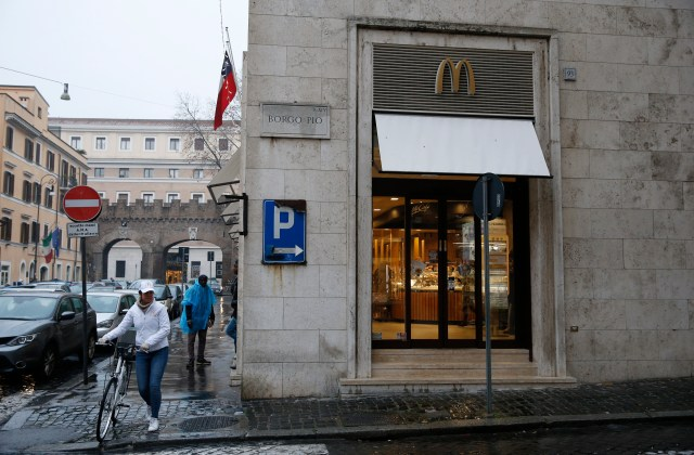 A worker crosses the street with her bike outside the newly opened McDonald's near the Vatican Jan. 12. (CNS/Paul Haring)
