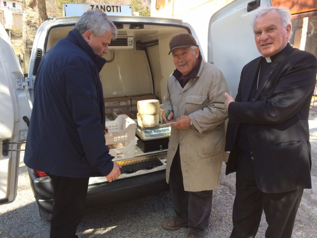 Archbishop Konrad Krajewski, the papal almoner, an unidentified merchant, and Archbishop Francesco Giovanni Brugnaro of Camerino-San Severino Marche, Italy, visit an area of central Italy affected by earthquakes. (CNS/Vatican Press Office)