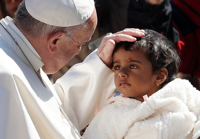 Pope Francis greets a child during his general audience in St. Peter's Square at the Vatican March 29. (CNS/Paul Haring)