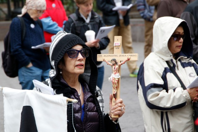 """A woman holds a crucifix during the 35th annual Pax Christi Metro New York Way of the Cross/Way of Peace April 14 in New York City. """"Jesus Calls Us to Active Nonviolence"""" was the theme of this year's Good Friday commemoration. (CNS/Gregory A. Shemitz)"""