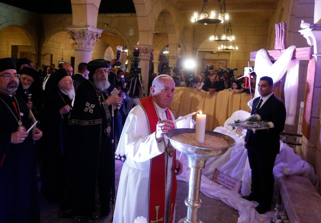 Pope Francis, accompanied by Coptic Orthodox Pope Tawadros II,  lights a candle outside St. Peter's Church in Cairo April 28. The pope lit the candle in remembrance of victims of a December 2016 bombing inside the church. (CNS/Paul Haring)