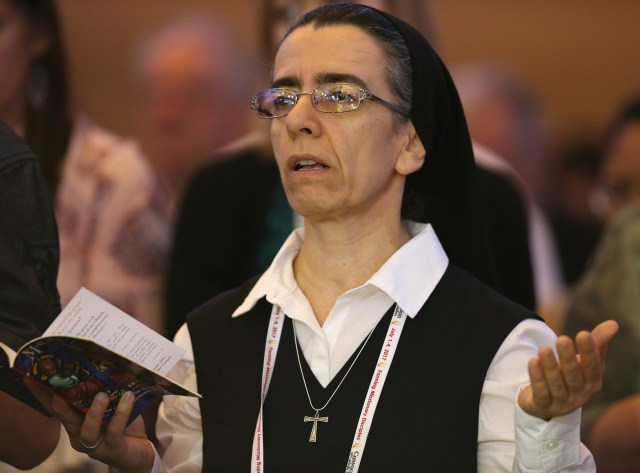 """A woman religious prays July 2 during the """"Convocation of Catholic Leaders: The Joy of the Gospel in America"""" in Orlando, Fla. Leaders from dioceses and various Catholic organizations gathered for the July 1-4 convocation. (CNS/Bob Roller)"""
