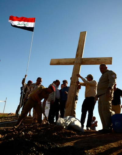People from Mosul, Iraq, raise a wooden cross near St. Georges Monastery April 24. Some Iraqi Christians who are making their slow return to ancestral lands say it will take time to rebuild their lives and trust of those who betrayed them. (CNS/EPA)